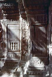 Relief depicting a barred window with almost completely lowered blinds and turned vertical bars.