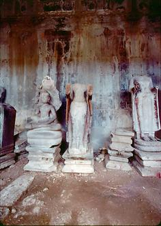 In one of the rooms a sitting and two headless standing Buddha statues were left by the Khmer Rouge.