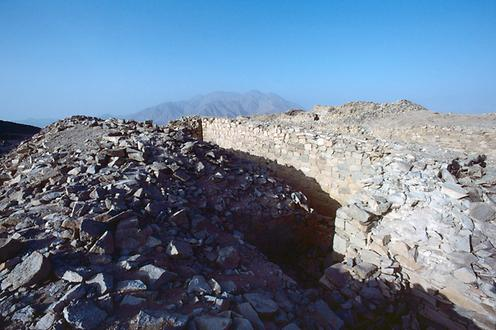 One of the double-angled gates of the inner defensive wall. In the background: Cerro Mucho Malo, a volcano.