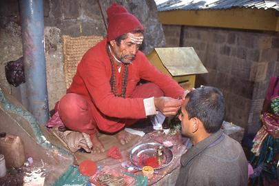 A Brahmin makes a red sign of blessing on the forehead of a pilgrim. His own forehead painting indicates that he is a follower of Shiva
